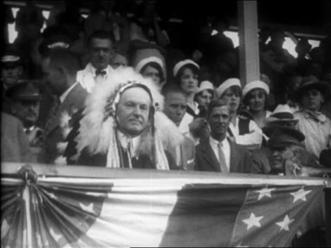 b/w 1927 pokerfaced calvin coolidge sitting in grandstand wearing headdress / newsreel - headdress stock videos & royalty-free footage