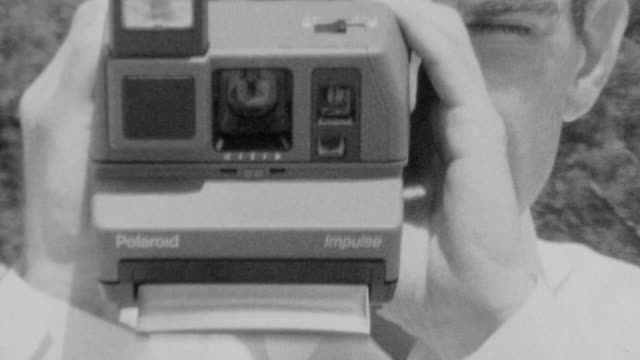 vidéos et rushes de polaroid snaps a picture and ejects roll film / man sits next too camera and picks it up / polaroid impulse instant camera on november 01 1989 in los... - appareil photo