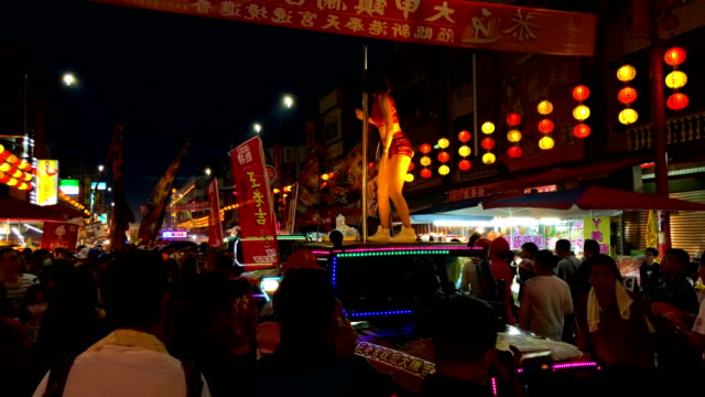Pole dancers perform on the roofs of cars as they take part in a parade near Xingang Fengtian Temple where the statue of Mazu will rest for two...