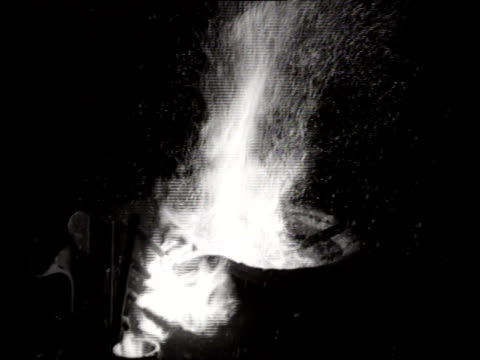 pole stirs a fire in a pot, creating sparks. - sparks点の映像素材/bロール