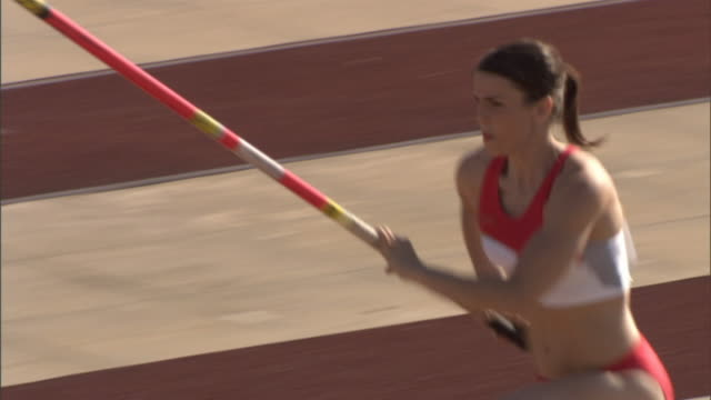 MS PAN Pole vaulter clearing bar, falling onto bag, and raising arm in victory/ Sheffield, England