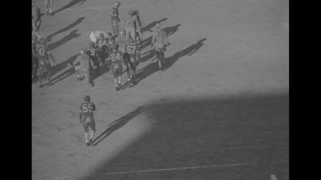 stockvideo's en b-roll-footage met a pole with pennants of washington and oregon / elevated views of the game in progress and tens of thousands watch from the grandstand / title card... - universiteit van washington