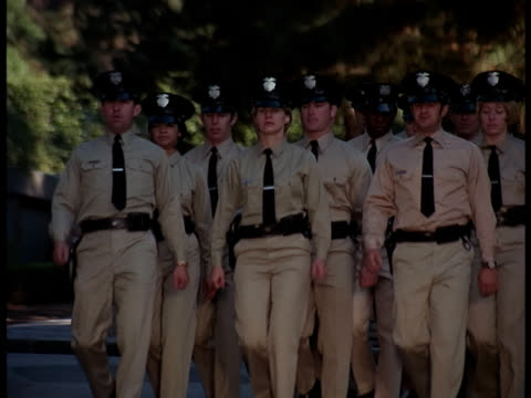 police academy    cadets marching to camera and by / man with bag runs l-r through academy gates - ufficiale grado delle forze armate video stock e b–roll