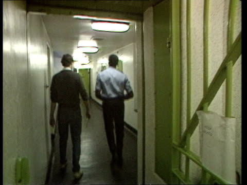 vídeos de stock, filmes e b-roll de police and criminal evidence act brings reforms of police powers r reading bv prisoner taken by policeman up corridor during reconstruction of arrest... - reading berkshire