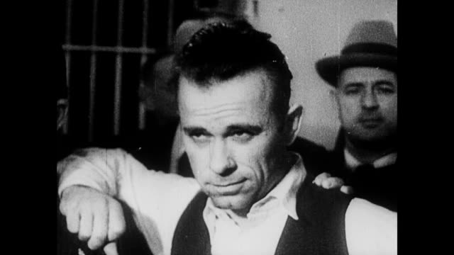 / police and cuffed criminals walk out of a building / cu john dillinger / man points out bullet holes on a car / dillinger's booking photo / several... - john dillinger stock-videos und b-roll-filmmaterial