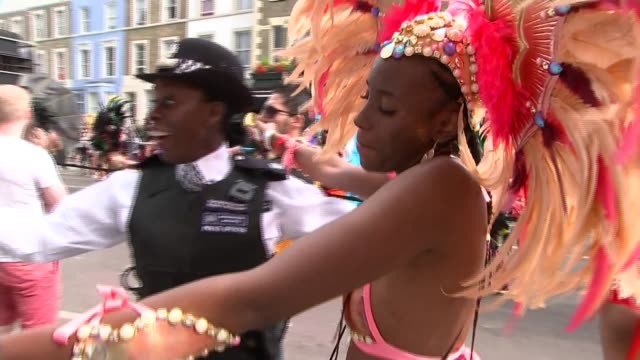 vídeos de stock e filmes b-roll de police and dancers at notting hill carnival police officers dancing with carnival dancers / police having photos taken with carnival dancers and... - notting hill