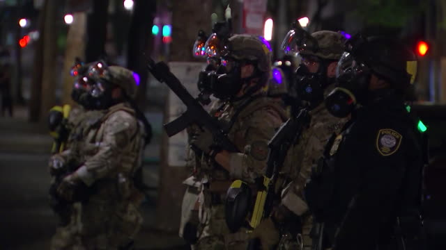 police and federal agents with riot gear and guns stand outside the federal courthouse in portland oregon - portland oregon stock-videos und b-roll-filmmaterial