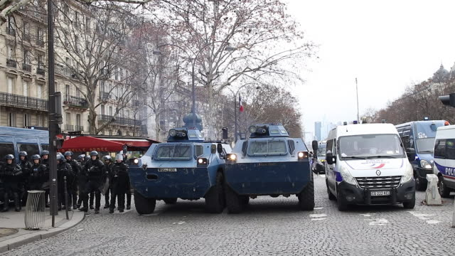 vídeos de stock, filmes e b-roll de police and gendarmerie forces with armored wheeled vehicle of the gendarmerie avenue of the great army near of arc de triomphe paris - vest