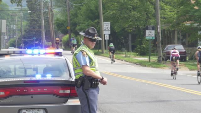 police and ironman cyclists - ansvar bildbanksvideor och videomaterial från bakom kulisserna