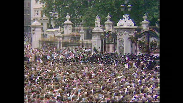 police and large crowds of spectators wait at the gates of buckingham palace on the day of the wedding of prince charles and lady diana spencer; 1981. - british culture stock videos & royalty-free footage