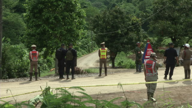 police and military provide security as the ambulances leaves the tham luang cave area after divers evacuated some of the boys among a group of 13... - chiang rai province stock videos and b-roll footage