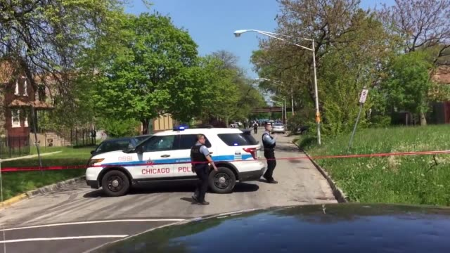 Police are seen grouped up with investigators at the scene Wide/CloseUp shots of active crime scene where a Chicago Police Officer was shot by female...