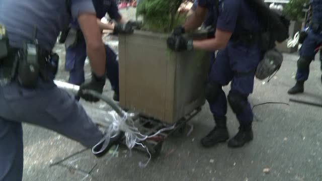Police armed with bolt cutters electric saws and sledgehammers make a renewed attempt to remove barricades along a stretch of the main protest site...