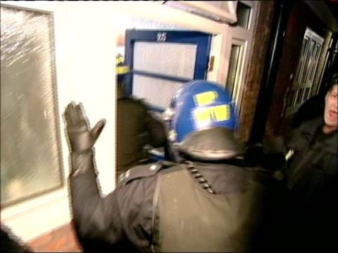 police arrest 8 in anti-gun raids; bbc london pool england: london: ext/night cbv police officers in riot gear entering house during anti-gun raids... - vest stock videos & royalty-free footage