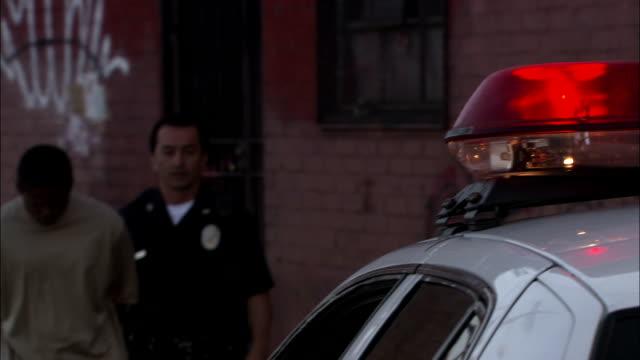police arrest a suspect and lead him to the patrol car. - suspicion stock videos & royalty-free footage