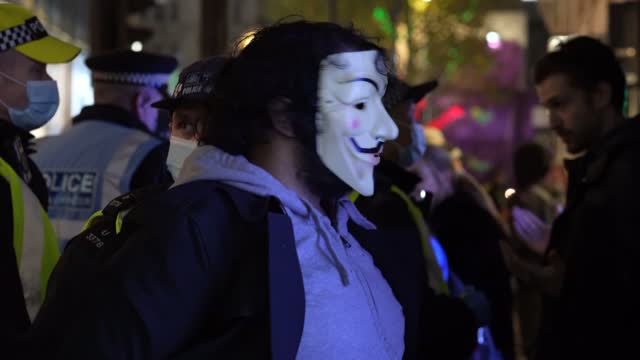 police arrest protester wearing a face mask synonymous with the activist group anonymous during the million masked march in central london on... - アノニマス点の映像素材/bロール