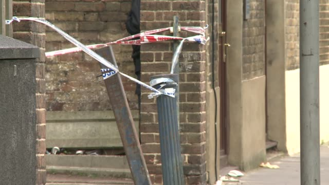London Bow EXT Police officers on street cordoned off with police tape / Closeup police tape / Bunsen Street sign / General views housing blocks in...