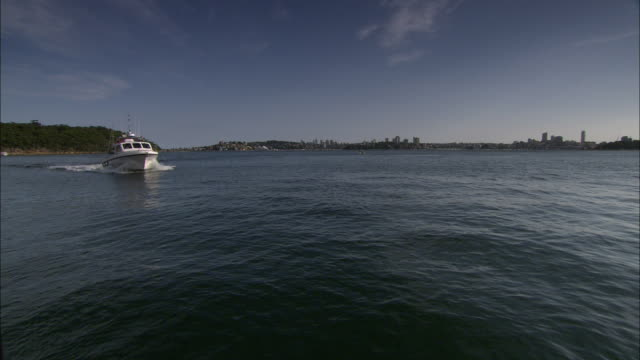 a police boat cruises across the harbor. - police boat stock videos and b-roll footage