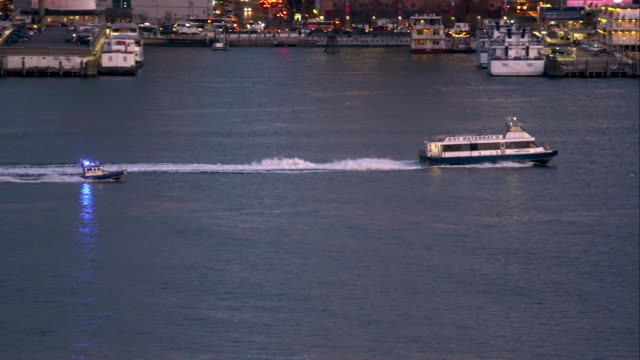 a police boat escorts a ferry down the hudson river in manhattan - police boat stock videos and b-roll footage