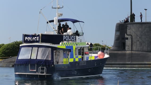 police boat protects the launch of the artful an astute class hunter killer nuclear powered submarine as it is moved from bae systems in barrow in... - tide stock videos & royalty-free footage