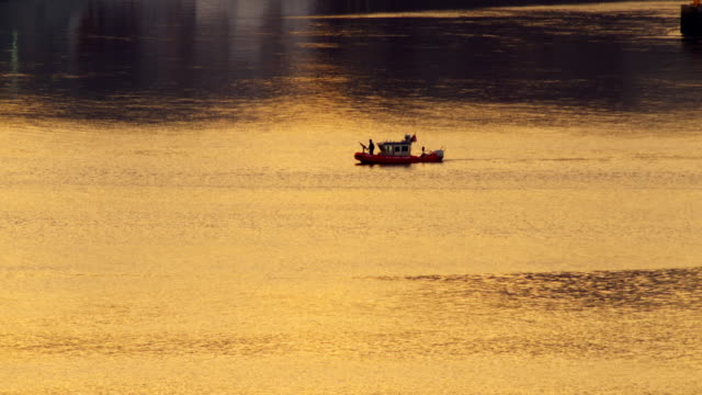 police boat slowly moves with the current of the hudson river. water reflects orange sky. - police boat stock videos and b-roll footage