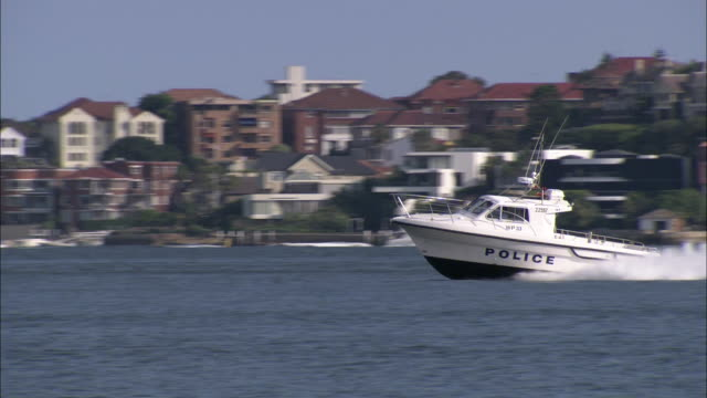 a police boat speeds across a harbor and past another ship. - officer stock videos and b-roll footage