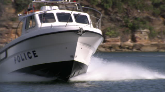 a police boat speeds across a harbor. - police boat stock videos and b-roll footage
