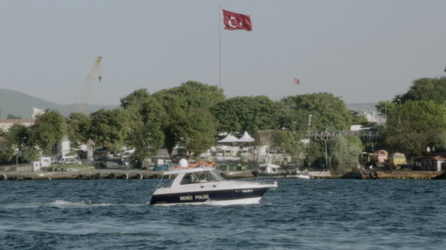 ts police boat traveling through a quiet harbor along the bosphorus strait with a turkish flag waving in the distance / istanbul, turkey - police boat stock videos and b-roll footage