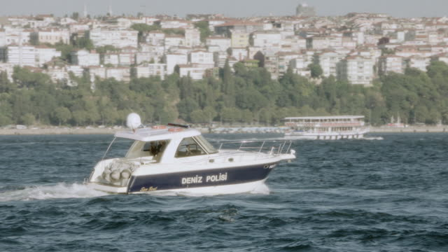 ts police boat traveling through a quiet harbor along the bosphorus strait / istanbul, turkey - police boat stock videos and b-roll footage