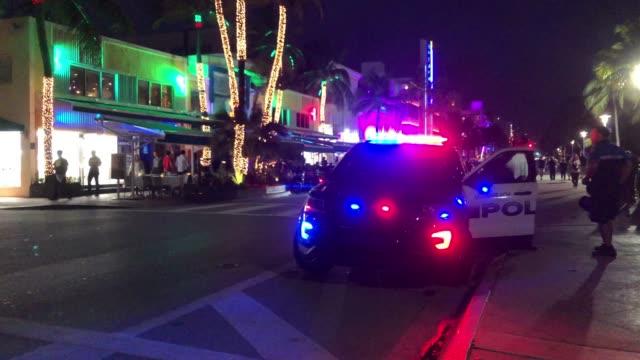 police car and miami beach restaurants at night - süden stock-videos und b-roll-filmmaterial