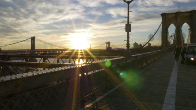Police car and people walking dog on top of Brooklyn bridge at Sunrise