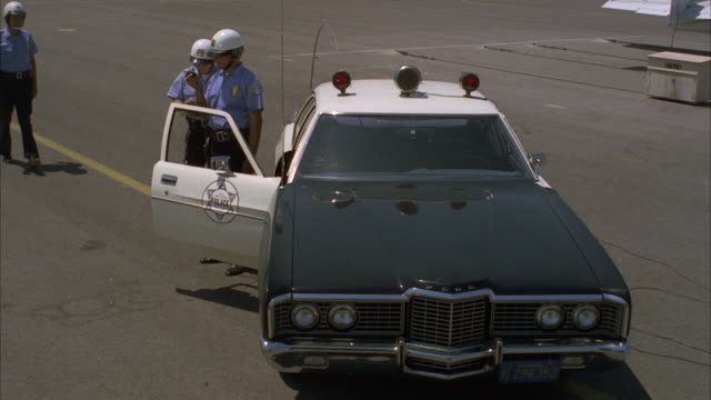 MS Police car being exploded on small airfield and policeman running at airport / Los Angeles, California, United States