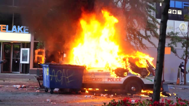 stockvideo's en b-roll-footage met police car burns during the george floyd protests. a police car burns outside of a building during the george floyd protests. - afvalcontainer container