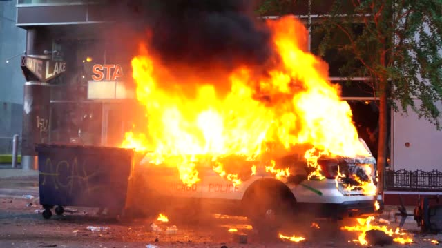 police car burns during the george floyd protests. a police car burns outside of a building during the george floyd protests. - burning stock videos & royalty-free footage