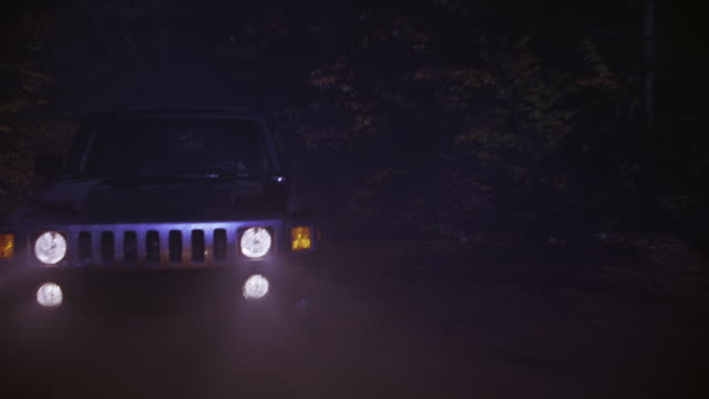 A police car chasing an SUV through a forest at night.