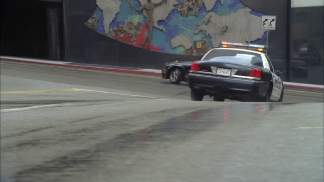 la. pan, police car chasing vehicle doing u-turn on city street, los angeles, california, usa - chasing stock videos & royalty-free footage