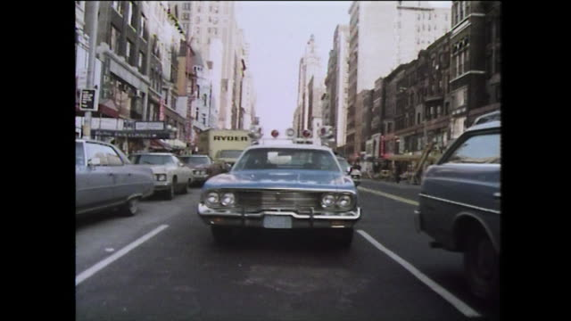 police car drives down a street in new york city; 1975 - 以前の点の映像素材/bロール