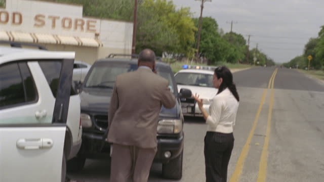ws ms police car driving toward scene of car accident, then officer approaches two people talking on road / elmendorf, texas, usa - rettungsdienst mitarbeiter stock-videos und b-roll-filmmaterial