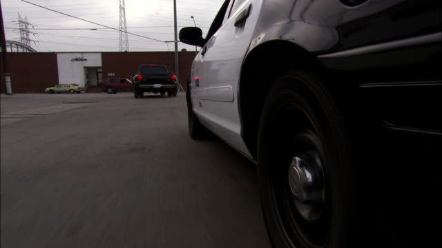 a police car follows a suspicious pickup truck through an industrial area. - suspicion stock videos & royalty-free footage