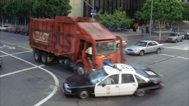ws police car gets hit on city street by garbage truck / los angeles, california, usa  - garbage truck stock videos and b-roll footage