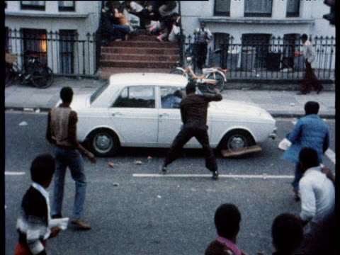 vídeos de stock e filmes b-roll de police car is stoned by young men car reverses hastily with windscreen smashed during disturbances at notting hill carnival london aug 76 - notting hill