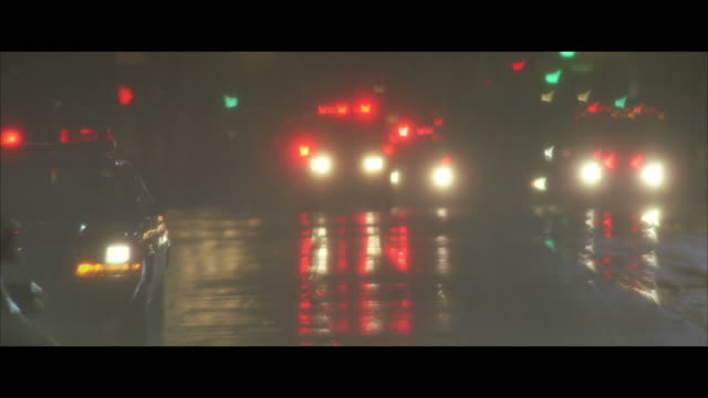 ms pan police car lights flashing, stopped at the middle of city street in rain - police vehicle lighting stock videos & royalty-free footage