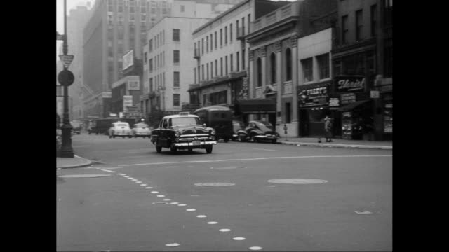 ws pan police car moving on lexington avenue crossing east 57th street in manhattan / united states - anno 1950 video stock e b–roll