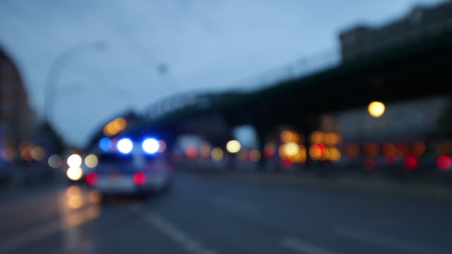police car night scene with bokeh lights and city traffic - blaulicht stock-videos und b-roll-filmmaterial