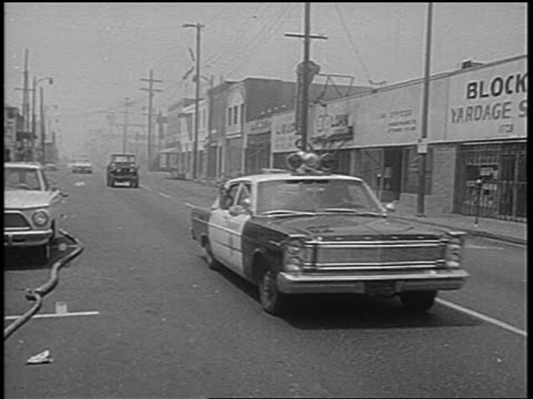 vídeos y material grabado en eventos de stock de pan police car on city street after watts race riots los angeles / newsreel - 1965