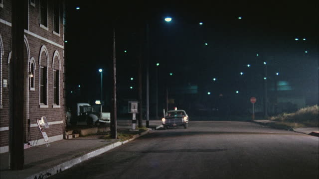 1966 ws police car on deserted street on outskirts of city at night - 1966 stock-videos und b-roll-filmmaterial