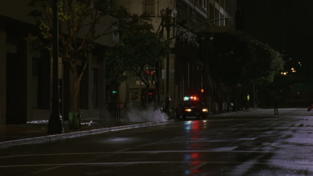 a police car parks behind several other police cars as officers run toward a dark storefront. - 追いかける点の映像素材/bロール