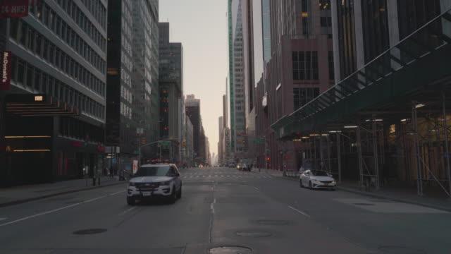 警車沿著紐約市最擁擠的目的地之一第六大道行駛,由於covid-19大流行爆發,現在該大道已經空無一人。 - 社會問題 個影片檔及 b 捲影像