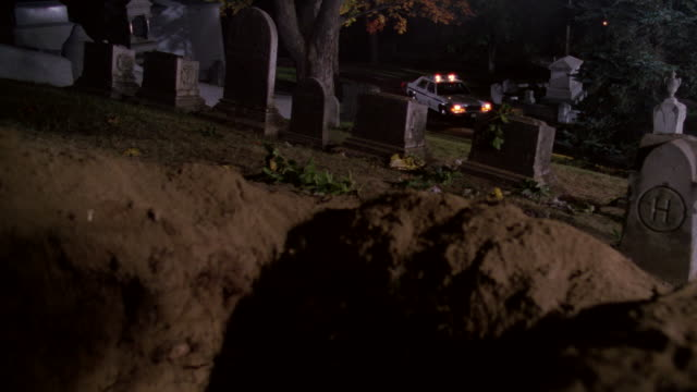 a police car shines a searchlight below an open grave on a hilltop. - grabstein stock-videos und b-roll-filmmaterial
