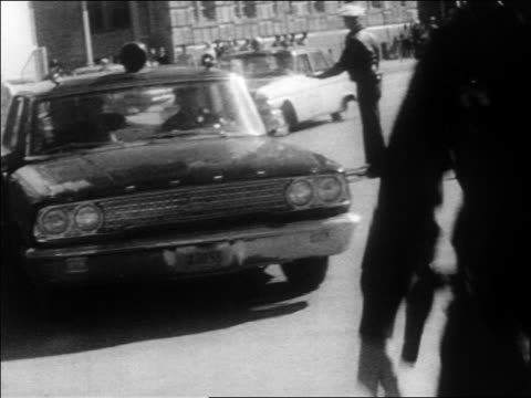 b/w 1963 police car stopping man getting out running / kennedy assassination / dallas - attentat auf john f. kennedy stock-videos und b-roll-filmmaterial